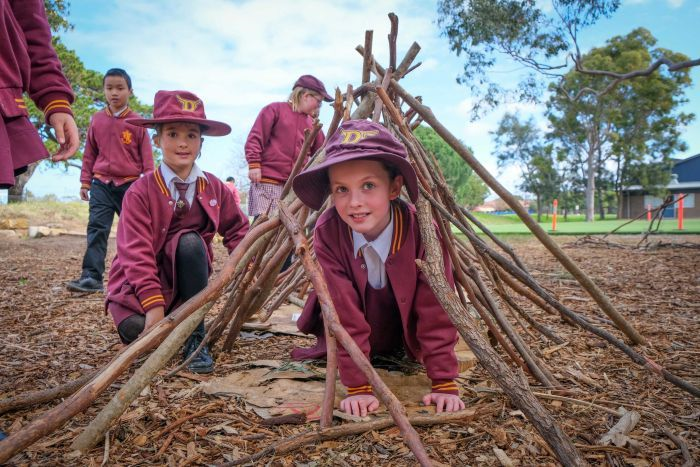 Students playing inside a den they have built from sticks